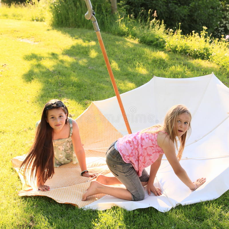 Two kids - girls playing on parasol royalty free stock images