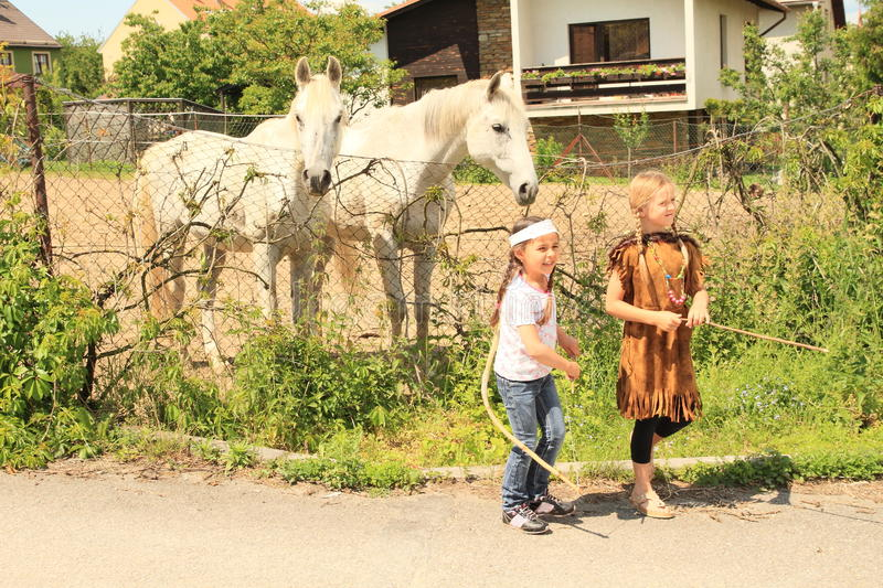 Two kids - girls walking from two horses royalty free stock image