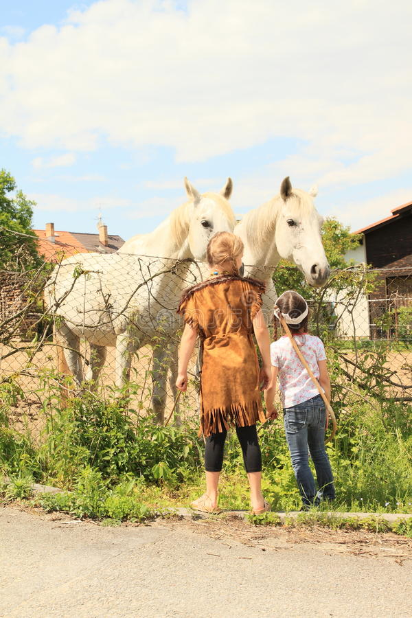 Two kids - girls watching two horses stock images