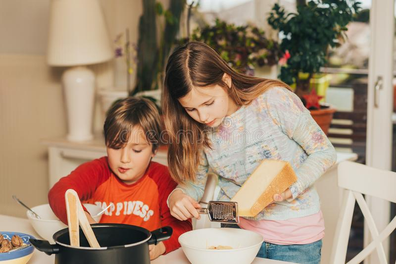 Two kids having spaghetti lunch at home, stock photo
