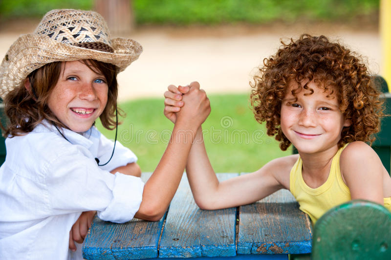 Two kids having wrist fight in park. Two boys having arm wrestle in park royalty free stock photography