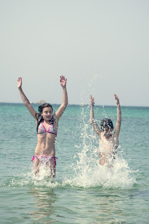Download Two Kids Jumping And Playing In The Ocean Stock Image - Image: 39894905
