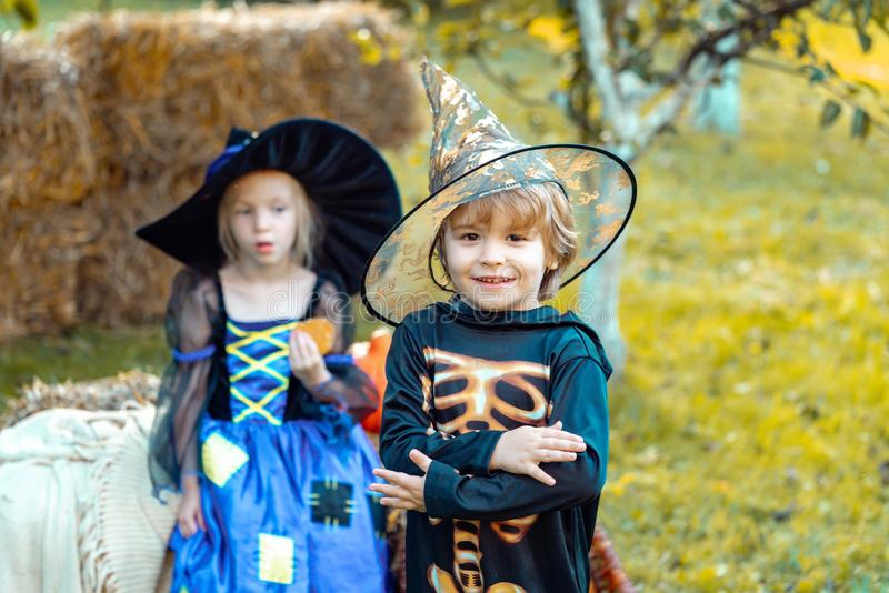Two kids like skeleton or witch Ready for Trick or Treat. Surprised group little zombie in Halloween costume eating stock photos