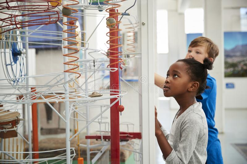 Two kids looking at a science exhibit, waist up stock images