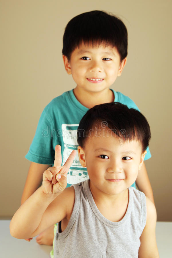 Two kids looking to the side. With one doing the victory sign royalty free stock photography