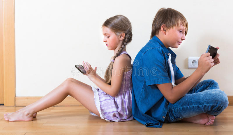 Two kids looking to smartphone screen stock photos