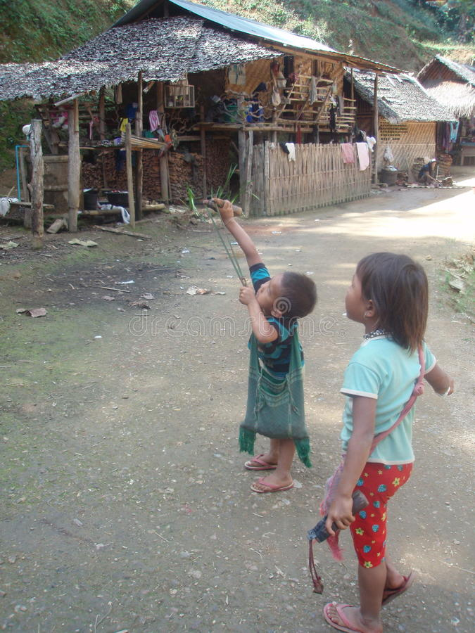 Two kids in Northern Thailand play with their slingshot. This picture was taking deep in the Thai jungle. This small village of approx. 25 inhabitants is right royalty free stock photography