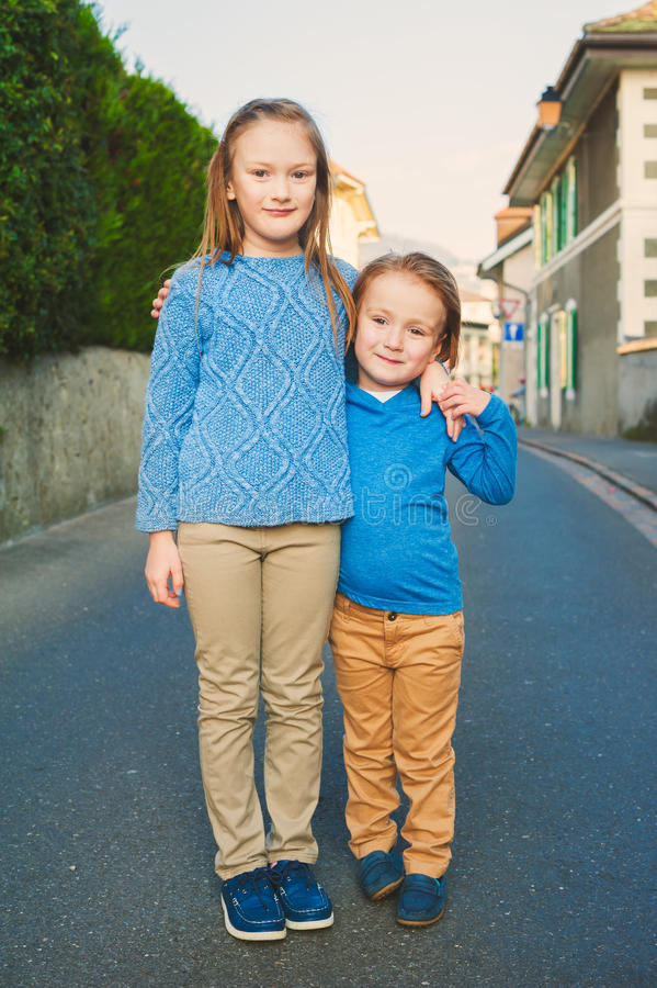 Two kids outdoors. Two adorable kids in a city, girl and her little brother, wearing blue and beige clothes and moccasins royalty free stock photos