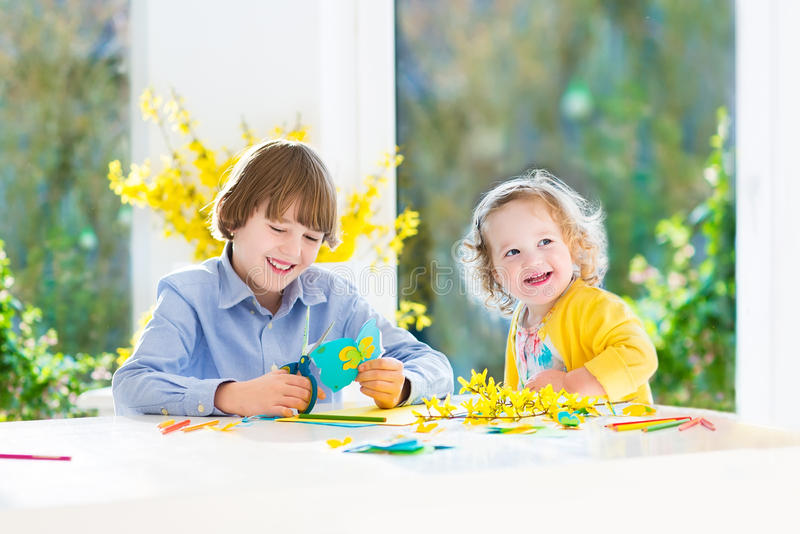 Two kids painting and cutting colorful paper butterflies royalty free stock photos