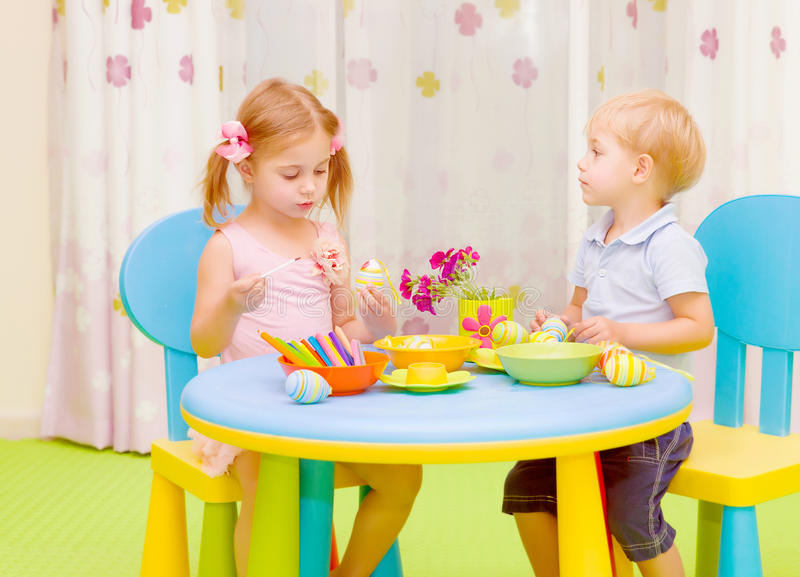Two kids painting Easter eggs stock photos