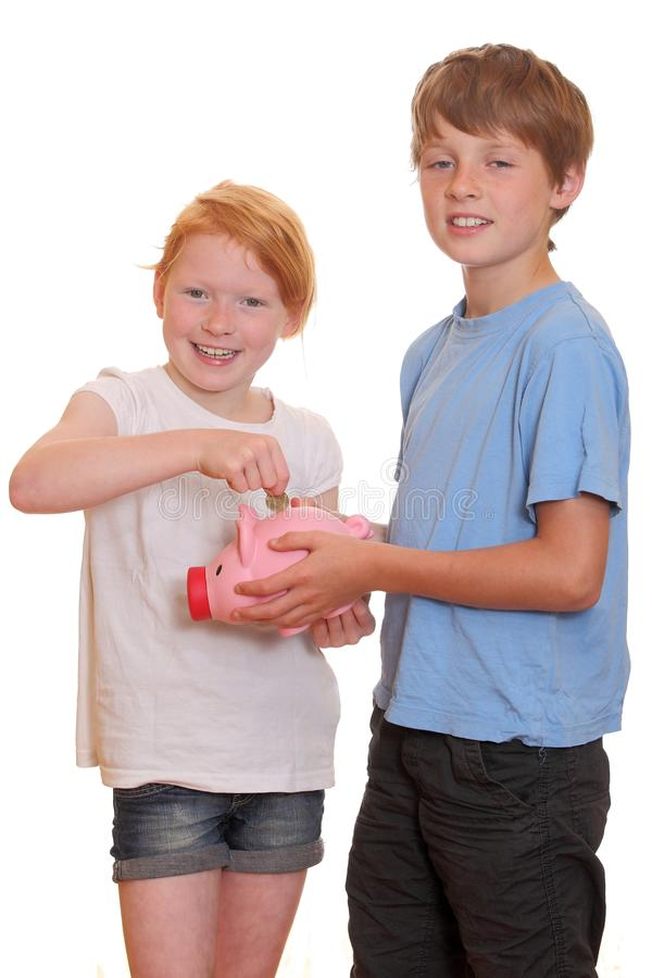 Two kids with piggy bank royalty free stock photo