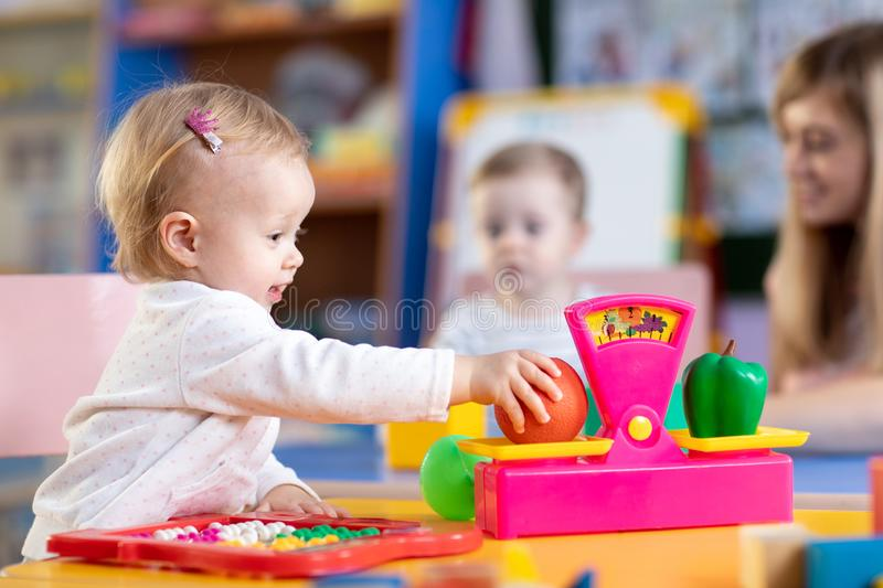 Two kids play role game in toy shop at home or kindergarten. Kids with preschool teacher play role game in toy shop at home or kindergarten royalty free stock photography