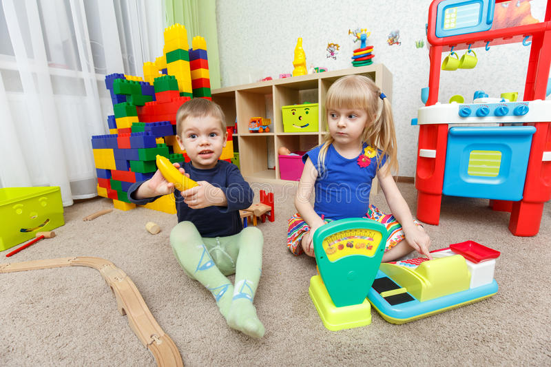 Two kids play role game in toy shop at home royalty free stock photos