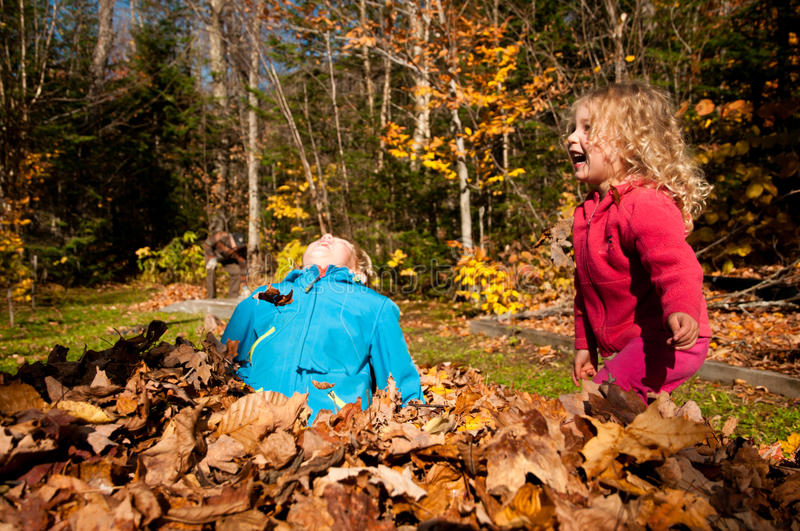 Two kids playing in autumn leaf stock photography