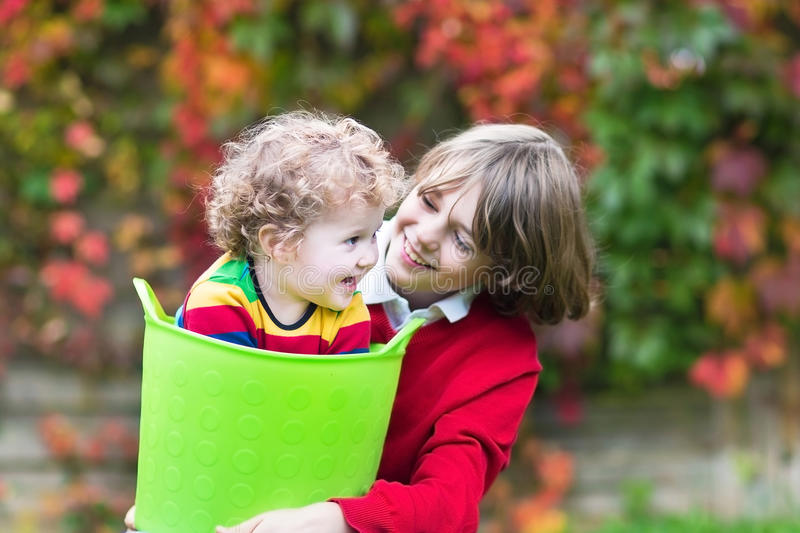 Two kids playing in garden with laundry basket stock photo