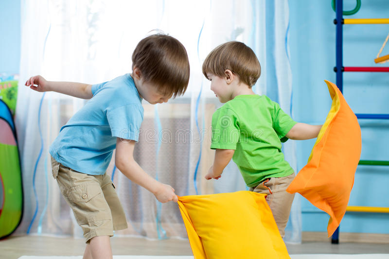 Two kids playing with pillows stock photography