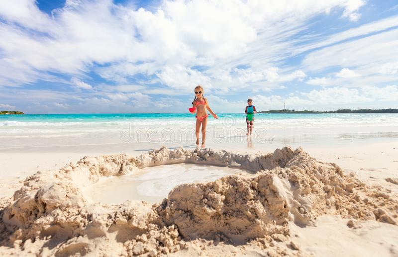 Two kids playing with sand. Brother and sister playing with sand at tropical beach stock image