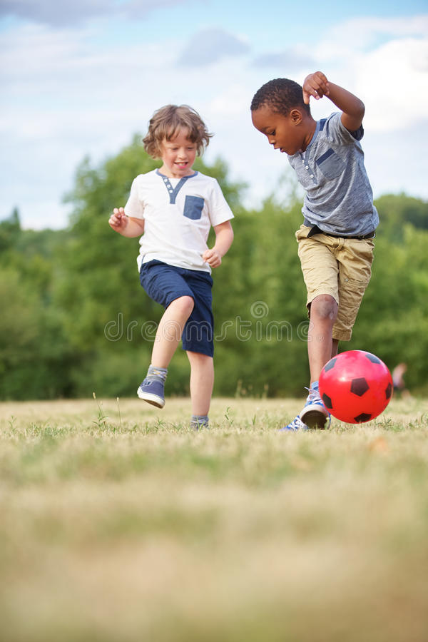 Two kids playing soccer stock image