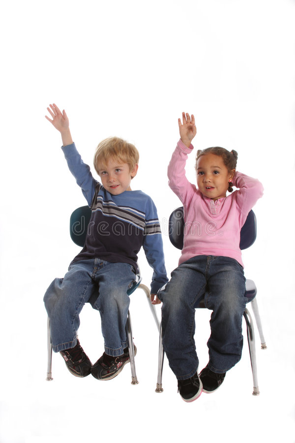 Two kids raising their hands in school. Two elementary school kids raising their hands to answer a question stock photography