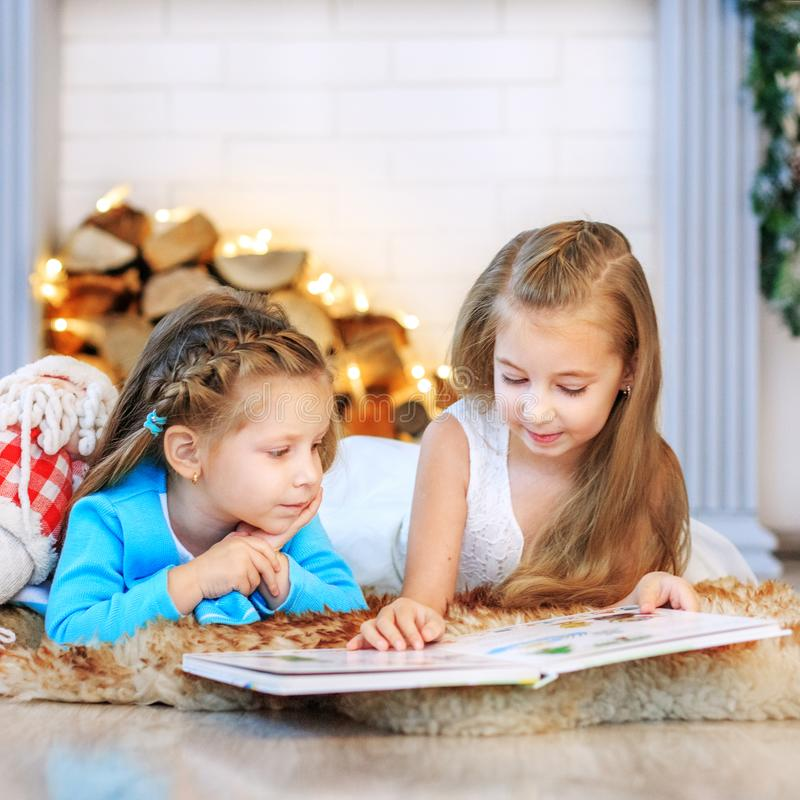 Two kids read a book. Concept New Year, Merry Christmas, holiday. Vacation, winter, childhood stock photos