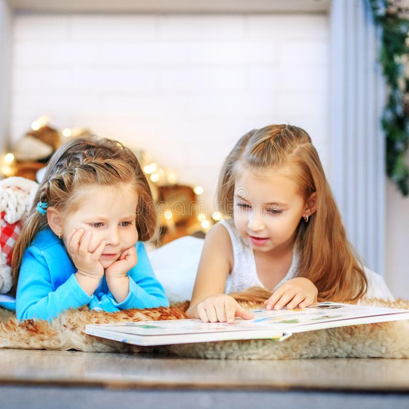 Two kids read a book. Two sisters. Concept New Year, Merry Chris. Tmas, holiday, vacation, winter, childhood royalty free stock image