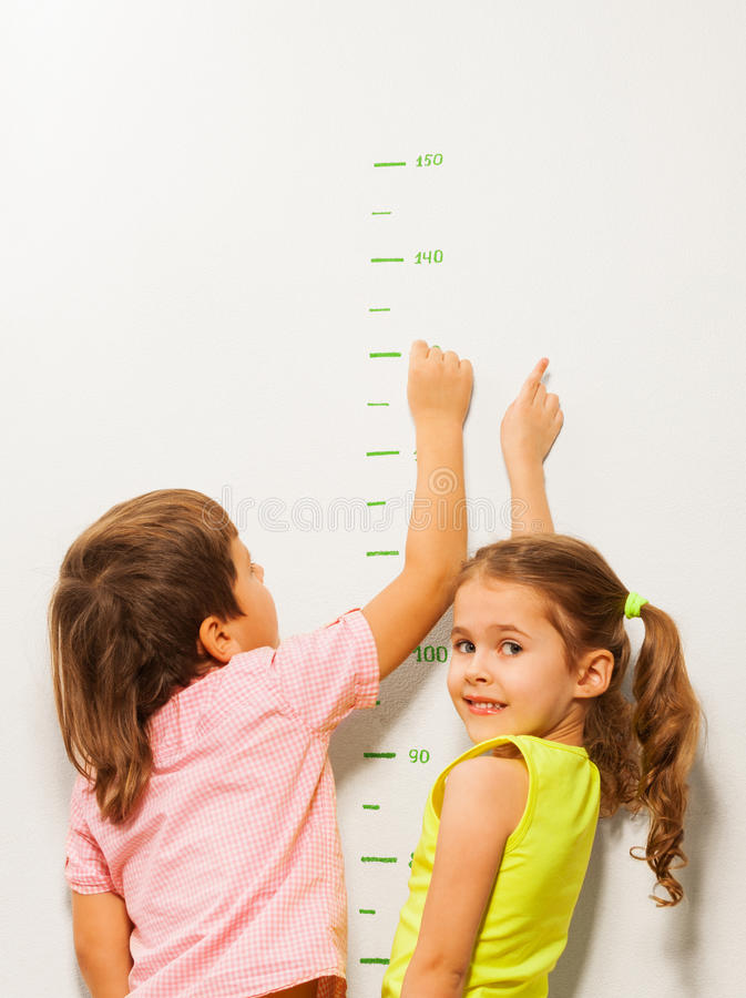 Two kids read height at home wall. Two little friends boy and girl read numbers on the wall royalty free stock photos