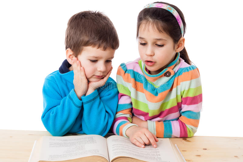 Two kids reading the book at the table stock images