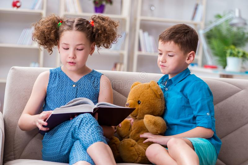 The two kids reading books at home. Two kids reading books at home stock photos
