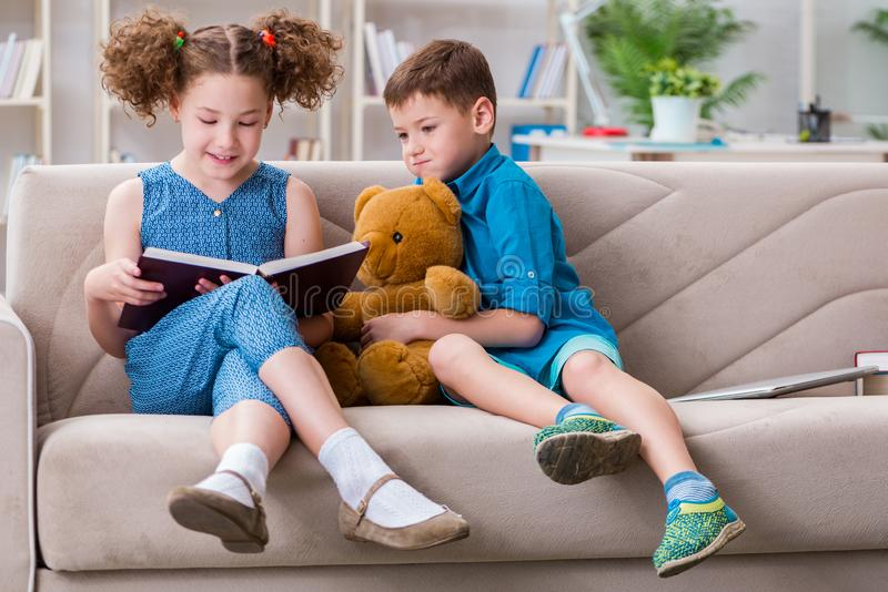The two kids reading books at home. Two kids reading books at home royalty free stock photo