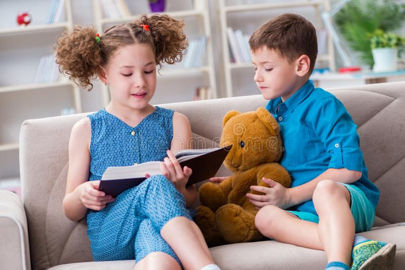 The two kids reading books at home. Two kids reading books at home stock photo