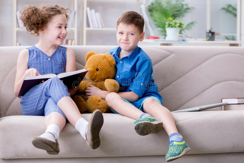 The two kids reading books at home. Two kids reading books at home royalty free stock photography