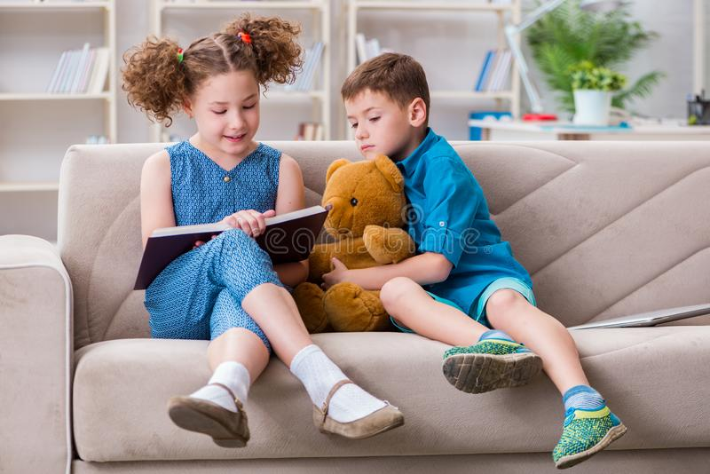 The two kids reading books at home. Two kids reading books at home stock photography