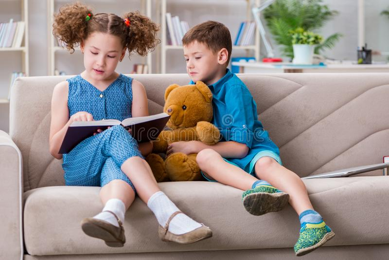 The two kids reading books at home. Two kids reading books at home royalty free stock image