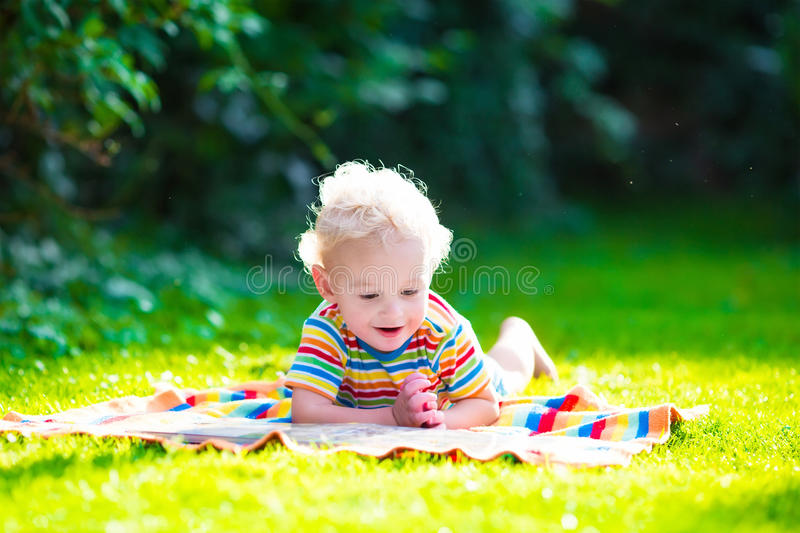 Two kids reading in summer garden. Kids reading a book in summer garden. Children study. Boy and girl play in school yard. Preschool friends playing and learning stock photo