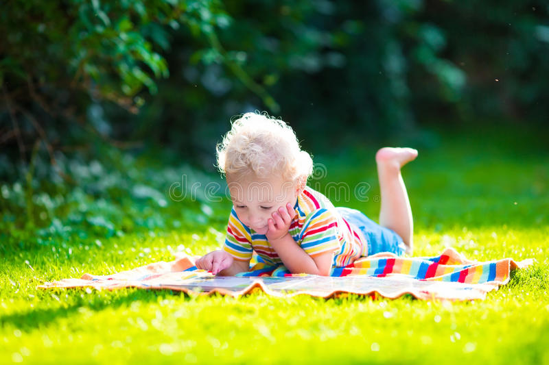 Two kids reading in summer garden. Kids reading a book in summer garden. Children study. Boy and girl play in school yard. Preschool friends playing and learning royalty free stock photography
