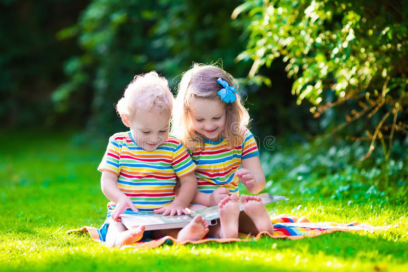 Two kids reading in summer garden. Kids reading a book in summer garden. Children study. Boy and girl play in school yard. Preschool friends playing and learning stock images