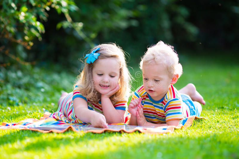 Two kids reading in summer garden. Kids reading a book in summer garden. Children study. Boy and girl play in school yard. Preschool friends playing and learning stock photos