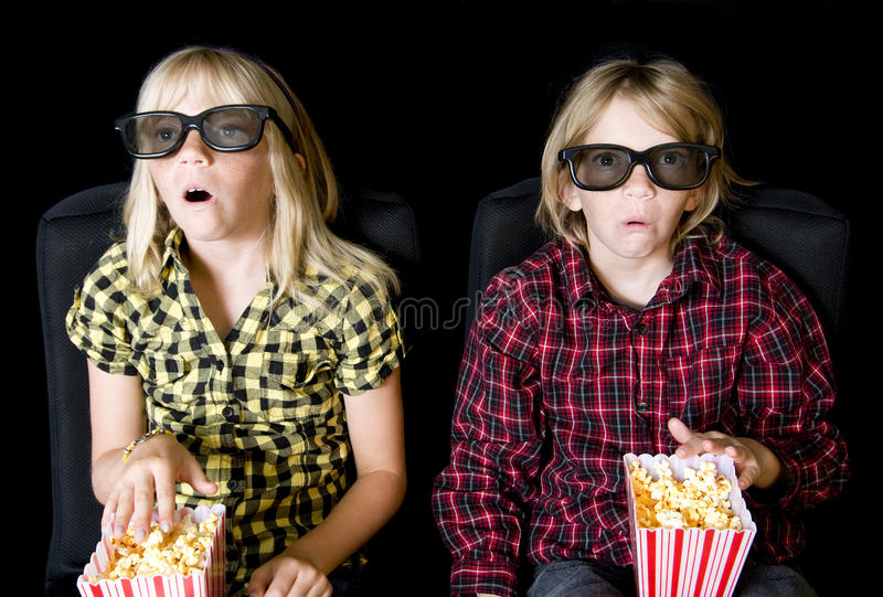 Two Kids at a Scary 3-D Movie stock photos