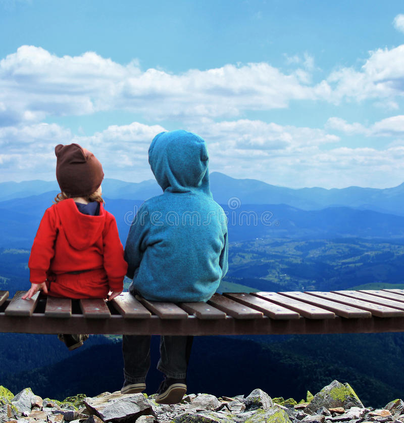 Two kids sitting on a bench, back view royalty free stock images