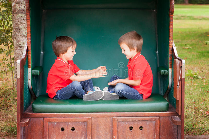 Two kids, sitting in a sheltered bench, playing hand clapping ga royalty free stock photos