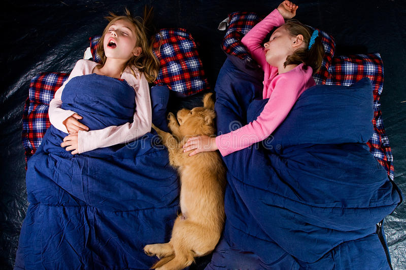 Two kids sound asleep in a tent royalty free stock photography