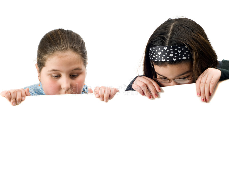 Two Kids Spying. Two young girls looking over a white wall at something stock photography
