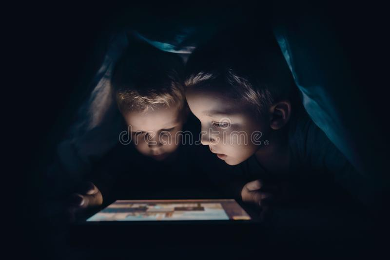 Two kids with tablet computer in a dark room stock images