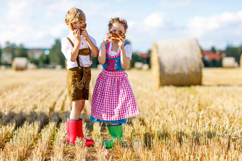 Two kids in traditional Bavarian costumes in wheat field. German children eating bread and pretzel during Oktoberfest stock photography