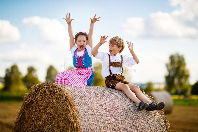 Two kids, boy and girl in traditional Bavarian costumes in wheat field with hay bales stock photo