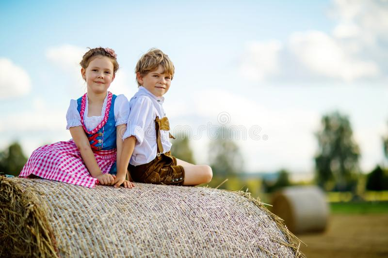 Two kids, boy and girl in traditional Bavarian costumes in wheat field with hay bales stock image