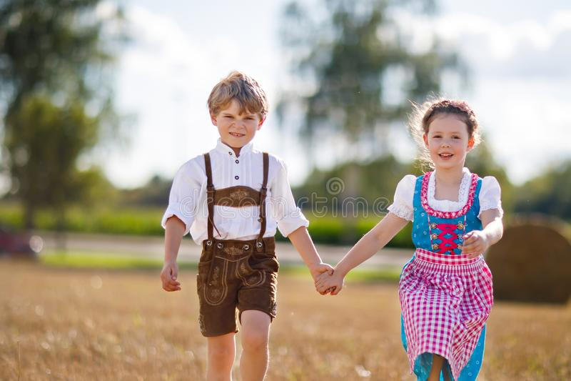 Two kids, boy and girl in traditional Bavarian costumes in wheat field with hay bales stock images