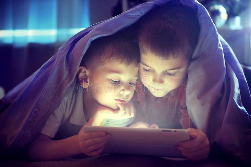 Two kids using tablet pc under blanket. At night royalty free stock images