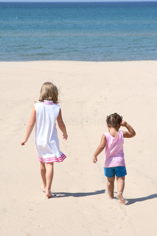 Two kids walking on the beach royalty free stock photography