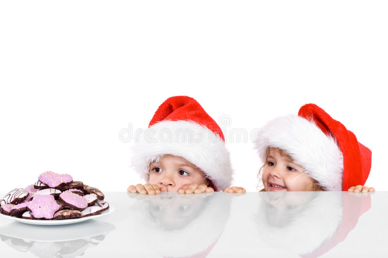 Two kids yearning for the christmas cookies. Isolated stock photo